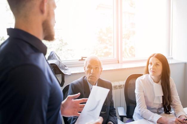 Człowiek daje wyjaśnienie do jego starszych ludzi biznesu w biurze