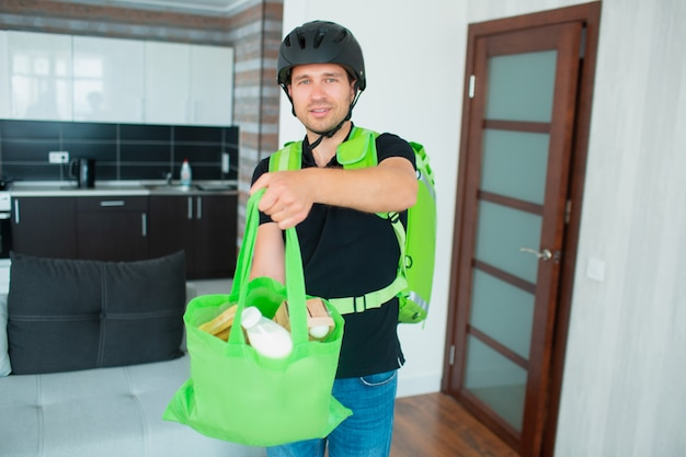 Człowiek dostarczający jedzenie przyniósł jedzenie do domu. on ma na sobie kask. ma plecak - lodówkę do dostarczania jedzenia.