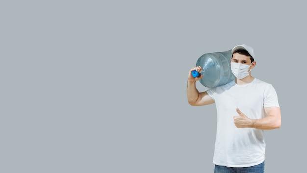 Człowiek dostarczający w masce ochronnej z dużą butelką.