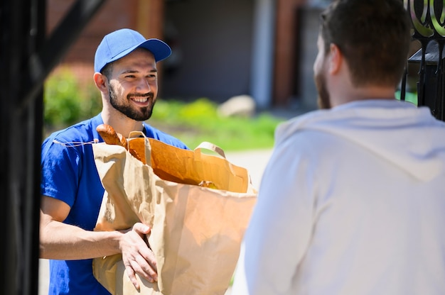 Człowiek dostawy chętnie rozdaje klientom produkty spożywcze