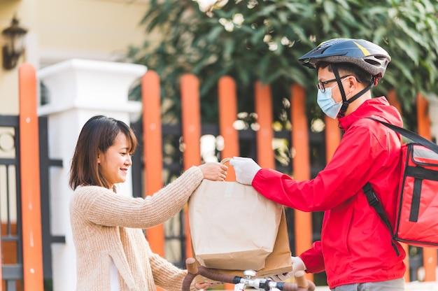 Człowiek dostawy, dając pudełka do młodych kobiet w domu, koncepcja usług kurierskich