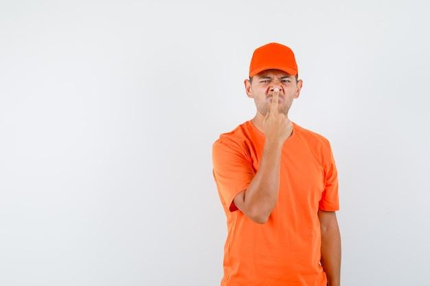 Człowiek dostawy dotykając nosem palcem w pomarańczowej koszulce i czapce i wyglądający ponuro