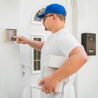 Człowiek dostawy klikając dzwonek