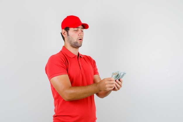 Człowiek dostawy liczenia banknotów dolara w czerwonej koszulce