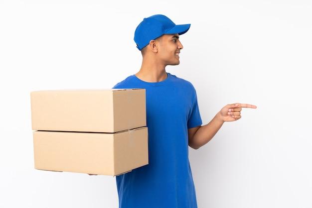 Człowiek dostawy na pojedyncze białej ścianie, wskazując na bok, aby przedstawić produkt