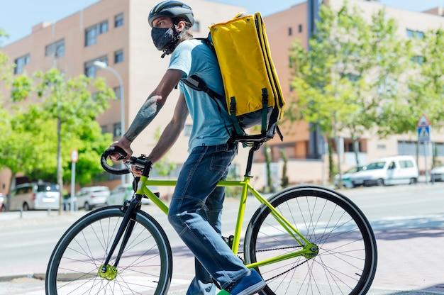 Człowiek dostawy na rowerze z maską