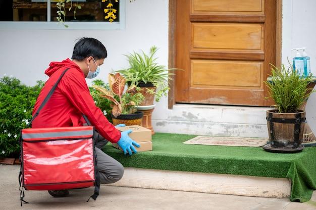 Człowiek dostawy na sobie niebieskie rękawiczki w czerwonym szmatką, trzymając pudełko