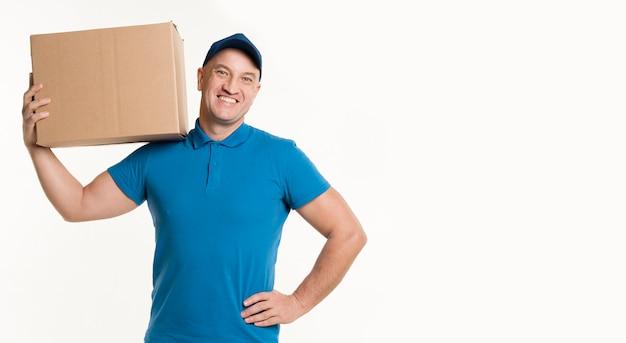 Człowiek dostawy niosąc karton