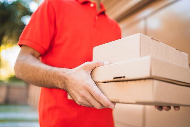 Człowiek dostawy niosący paczki podczas dostawy do domu.