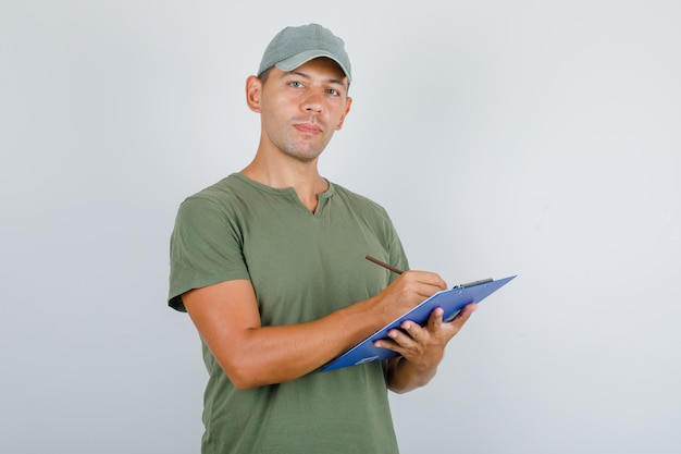 Człowiek dostawy notatek w schowku w armii zielony t-shirt, czapka, widok z przodu.