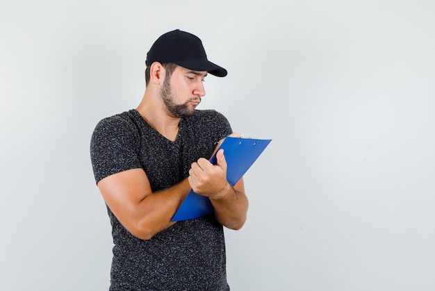 Człowiek dostawy notatek w schowku w t-shirt i czapkę i patrząc zajęty