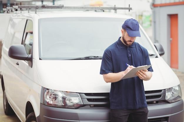 Człowiek dostawy pisania w schowku przed jego van