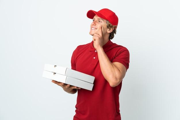 Człowiek dostawy pizzy nad białym myśli pomysł, patrząc w górę
