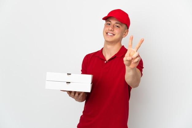 Człowiek dostawy pizzy w mundurze pracy, zbierając pudełka po pizzy na białej ścianie, uśmiechając się i pokazując znak zwycięstwa