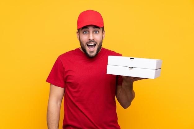 Człowiek dostawy pizzy w mundurze roboczym, zbierając pudełka po pizzy na żółtej ścianie z zaskoczeniem i zszokowanym wyrazem twarzy
