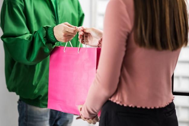 Człowiek dostawy, podając towar do klienta