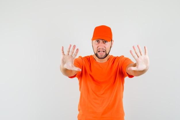 Człowiek dostawy pokazując gest zatrzymania w pomarańczowy t-shirt, czapkę i patrząc przestraszony, widok z przodu.