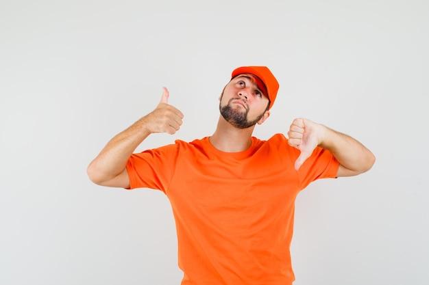 Człowiek dostawy pokazując kciuk w górę iw dół w pomarańczowy t-shirt, czapkę i patrząc zdezorientowany. przedni widok.