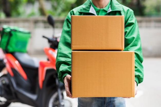 Człowiek dostawy posiada pudełka na zakupy