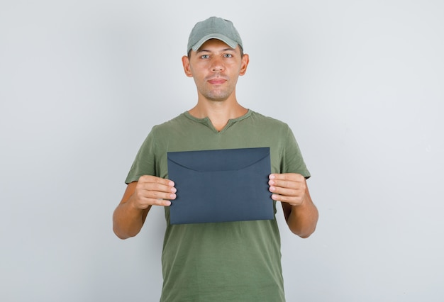 Człowiek dostawy posiadający paczkę w wojskowej zielonej koszulce, czapka, widok z przodu.