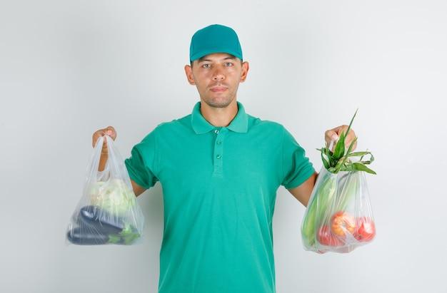Człowiek dostawy posiadający torby polietylenowe z warzywami w zielonej koszulce z czapką