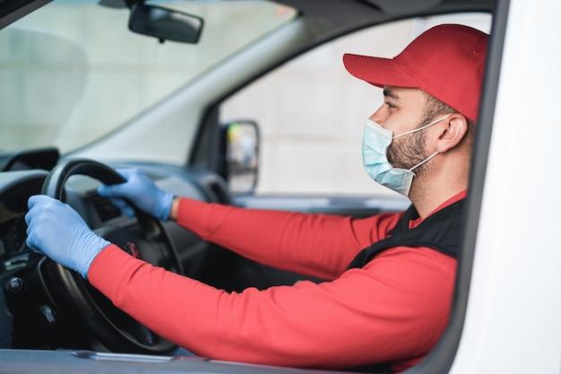 Człowiek dostawy prowadzący samochód dostawczy z paczkami do klientów - skupienie się na twarzy