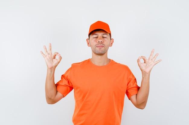 Człowiek dostawy robi ok znak z zamkniętymi oczami w pomarańczowej koszulce i czapce i wygląda spokojnie