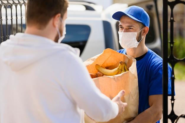 Człowiek dostawy rozdaje produkty spożywcze klientowi