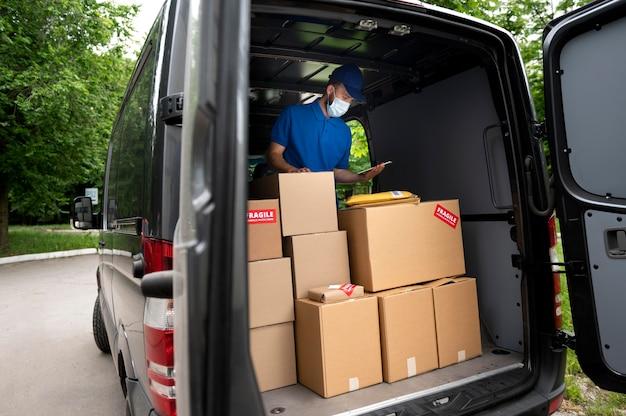 Człowiek dostawy średniego strzału w furgonetce
