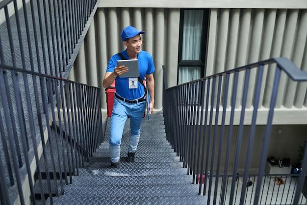 Człowiek dostawy szuka odpowiedniego mieszkania w budynku