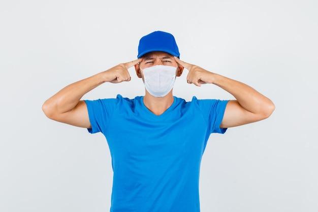 Człowiek dostawy, trzymając palce na skroniach w niebieskiej koszulce