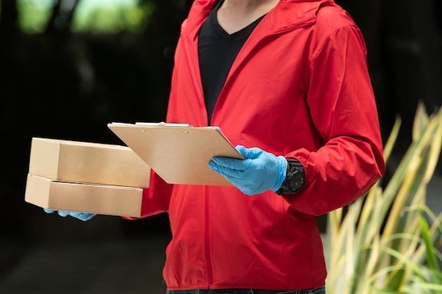 Człowiek dostawy ubrany w niebieskie rękawiczki i czerwoną kurtkę, trzymając kartony