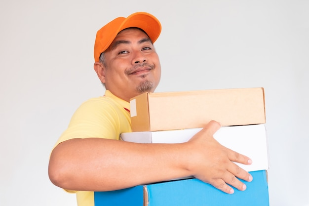 Człowiek dostawy w czapce pomarańczowej i żółtej koszuli przenoszenia paczki pocztowej wysyłanie do odbiorcy