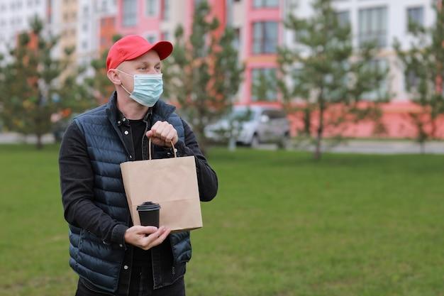 Człowiek dostawy w czerwonej czapce, maska medyczna na twarz trzyma papierową torbę i pije w jednorazowym kubku na zewnątrz w mieście