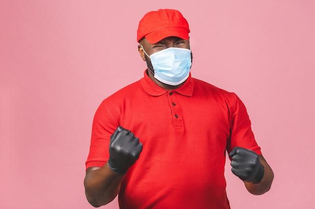 Człowiek dostawy w czerwonej czapce pusty t-shirt jednolite sterylne rękawiczki maski na twarz. facet pracujący kurierem
