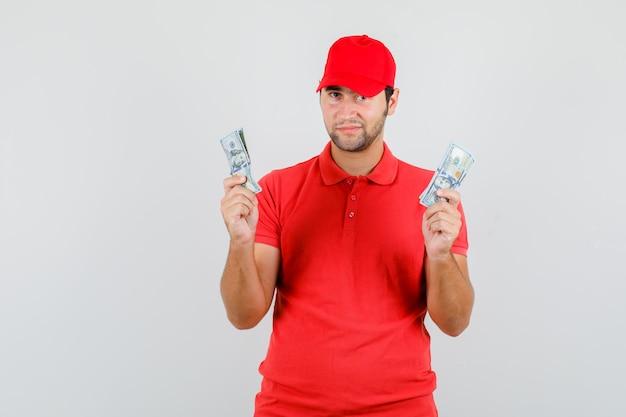 Człowiek dostawy w czerwonej koszulce, czapce trzymającej banknoty dolara i patrząc pozytywnie