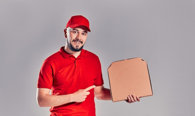 Człowiek dostawy w czerwonym kapturku, t-shirt, dając pudła pizzy zamówienia żywności na białym tle na szarym tle. mężczyzna pracownik pizzaman kurier trzyma pizza w pustej pustej przestrzeni kartonowej płaskiej przestrzeni kopii. koncepcja usługi