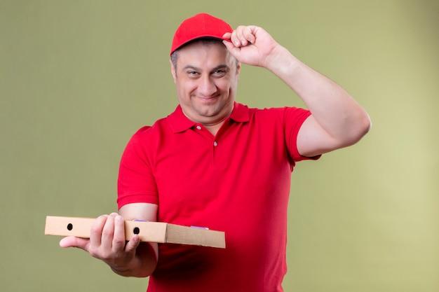 Człowiek dostawy w czerwonym mundurze i czapce trzyma pudełka po pizzy pozytywne i szczęśliwe dotykając jego czapki uśmiechając się przyjaźnie stojąc na odizolowanej zieleni