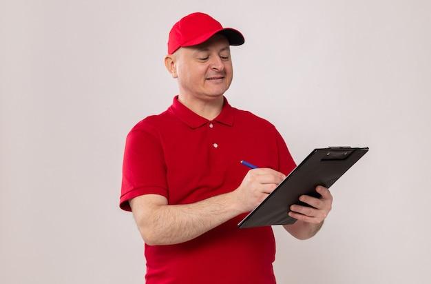Człowiek dostawy w czerwonym mundurze i czapce, trzymając schowek i długopis, sporządzając notatki, uśmiechając się pewnie stojąc na białym tle