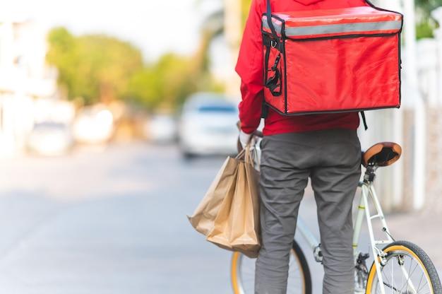 Człowiek dostawy w czerwonym mundurze jazda rowerem do dostarczania produktów klientom w domu.