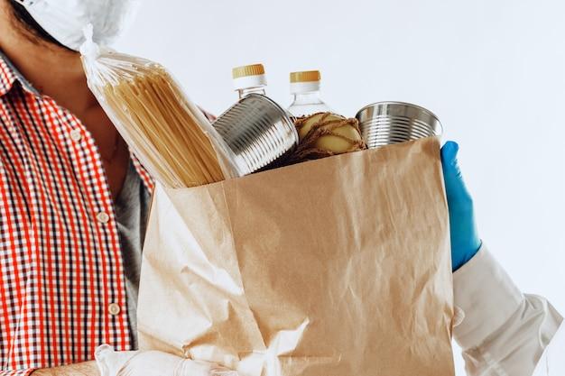 Człowiek dostawy w masce i rękawiczkach. dostawa żywności, koncepcja zakupów online podczas pandemii koronawirusa na całym świecie