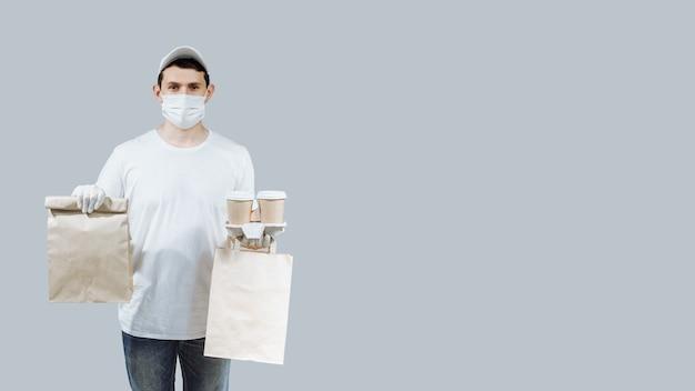 Człowiek dostawy w masce i rękawiczkach z papierową torbą i filiżankami kawy