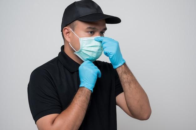Człowiek dostawy w masce ochronnej i rękawicach gumowych