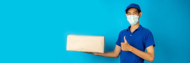 Człowiek dostawy w masce, trzymając paczkę