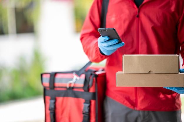 Człowiek dostawy w niebieskich rękawiczkach w czerwonej szmatce szuka adresu klienta przez telefon komórkowy