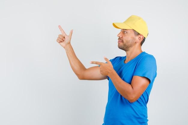 Człowiek dostawy w niebieskiej koszulce, czapka wskazująca na bok z gestem pistoletu
