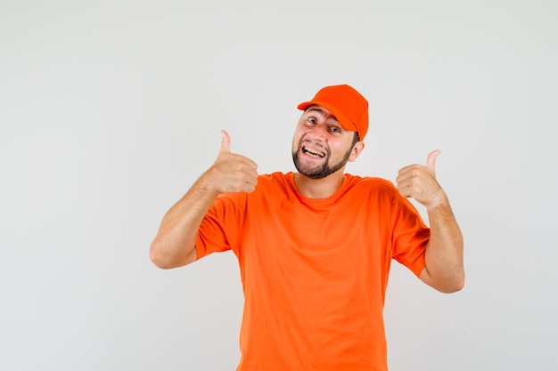 Człowiek dostawy w pomarańczowy t-shirt, czapka pokazująca podwójne kciuki w górę i patrząc wesoło, widok z przodu.
