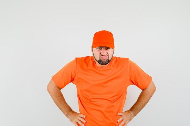 Człowiek dostawy w pomarańczowy t-shirt, czapka trzymając się za ręce w talii i patrząc uparty, widok z przodu.