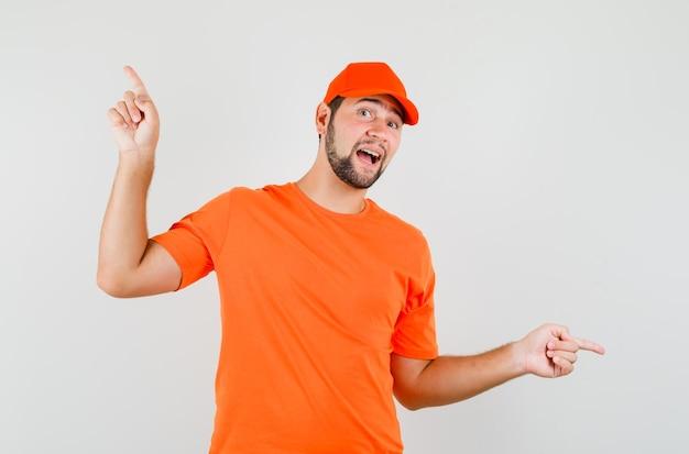 Człowiek dostawy w pomarańczowy t-shirt, czapka wskazująca palce w górę iw dół i patrząc optymistycznie, widok z przodu.
