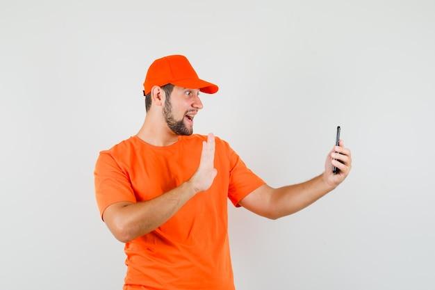 Człowiek dostawy w pomarańczowy t-shirt, macha ręką czapkę na wideorozmowę i wygląda wesoło, widok z przodu.